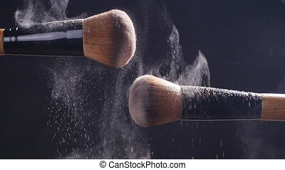 Two makeup brushes with powder on a dark background - Two...
