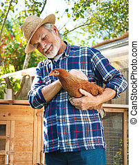 Farmer holds chicken in his arms in front of hen house -...