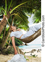 in hammock - view of nice woman lounging in hammock in...