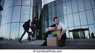 Fired businessman sitting on street - Fired business man...