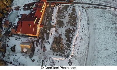 Aerial shot of village with houses and snowy fields in...