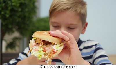 child eating a bun with chicken, cheese and greens in a fast...
