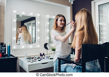 Caucasian beautician wearing casual clothes engaged on...