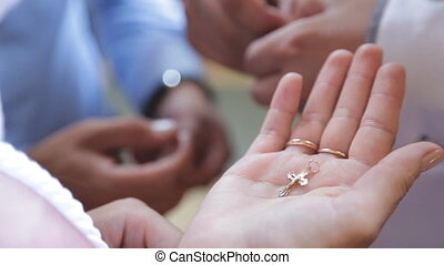 Young woman holds gold cross in hand before ceremony of...
