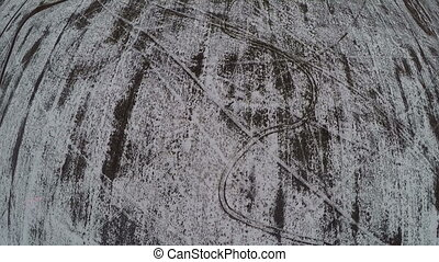 Flat snowy ground with car tracks, aerial shot - Aerial view...