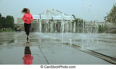 Super slow motion shot of a young mixed race happy woman running in the rain near city park fountains