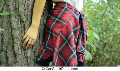 sensual girl with her eyes closed stands near the tree the...