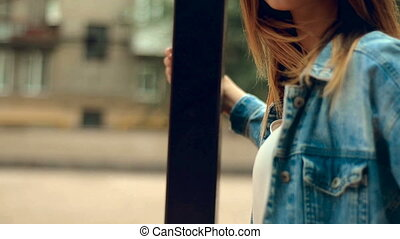young blonde with red lips stands near a pillar in the city