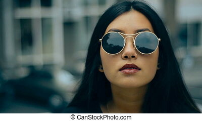 close up of beauty asian brunette in sunglasses in the city