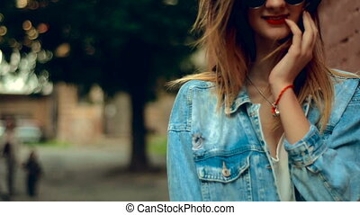 beautiful blonde woman with red lips walks at the brick wall...