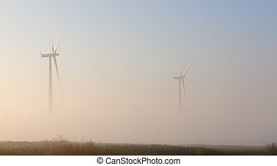 Wind turbines in the mist at dawn in southern Ontario