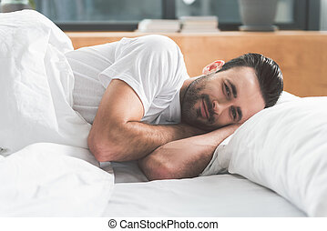 Joyful guy awakes in comfortable bed - Good morning....