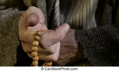 Old man holding prayer beads in hand.
