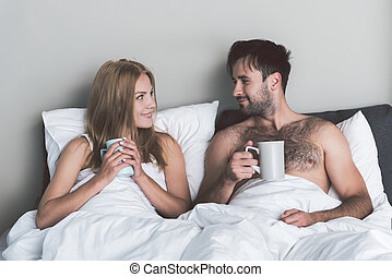 Cheerful man and woman enjoying hot drink in bedroom -...