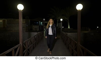Cheerful blonde young woman in leather jacket walks alone on...