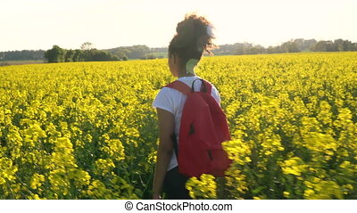 Young woman hiking with red backpack in field of rape seed...
