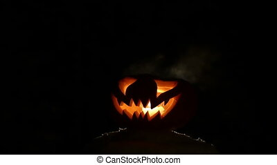 Carved Halloween pumpkin lights inside with flame on a black...