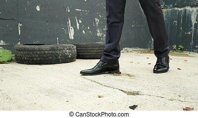 Men's classic black shoes against the collapsing wall....