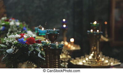 Burning candles in candlesticks and flowers in interior of...