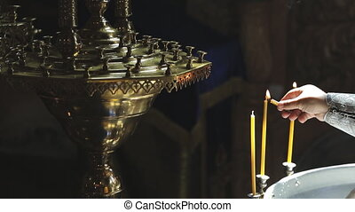 clergyman lights candles and puts on candlestick in church...