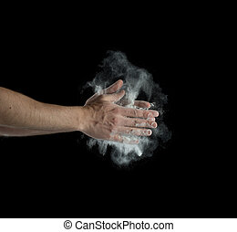 Freeze motion of dust explosion in hands isolated on black...