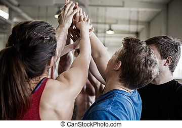 Fit People Giving High Five To Each Other In Gymnasium -...