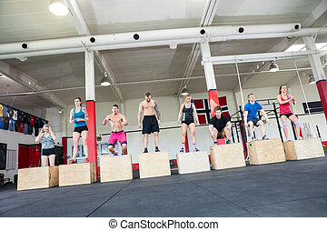 Athletes Practicing Box Jumps In Gym - Tilt image of male...