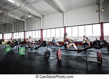 Female And Male Athletes Using Rowing Machine - Determined...