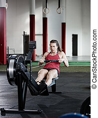 Fit Woman Exercising On Rowing Machine - Full length of fit...