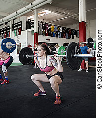 Woman Lifting Barbell With Friends In Gym