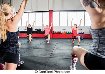Friends With Arms Raised Exercising In Gym