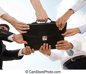 Struggle - Photo of human hands touching a black briefcase