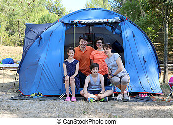 cheerful five-person family with three children with camping...
