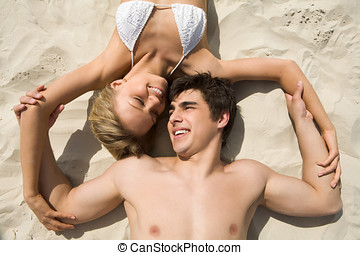 Paradise - Above shot of amorous couple relaxing on sandy...
