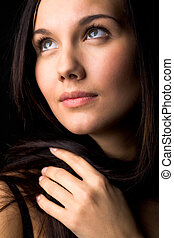 Femininity - Image of young female with dark hair touching...