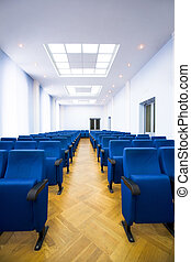 Conference hall - Image of several rows of dark blue...