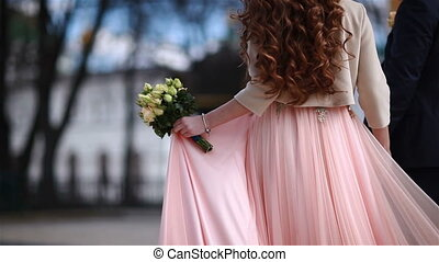 The bride goes in a pink dress and with a bouquet of yellow flowers