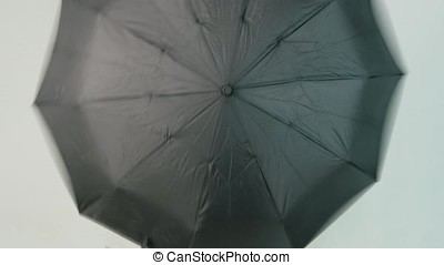 Young woman openes black umbrella on white background