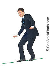 Young businessman walking on tightrope - Young businessman...