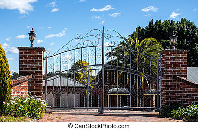 Metal driveway security entrance gates set in brick fence with residential garden in background against blue sky