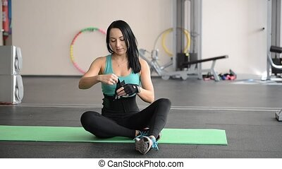 beautiful sports girl puts on gloves on hand before training