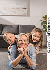 happy family lying on floor - happy grandfather and...
