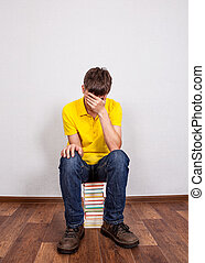 Sad Young Man with a Books on the Floor in the Room