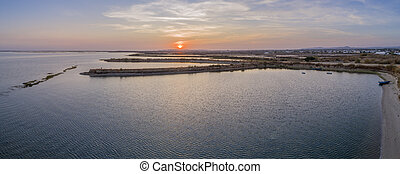 Sunset aerial panoramic seascape view of Olhao salt marsh...