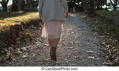 Young beautiful woman walking in the part at bright sunny...