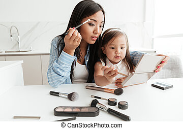Young pretty asian woman doing make up while sitting with...