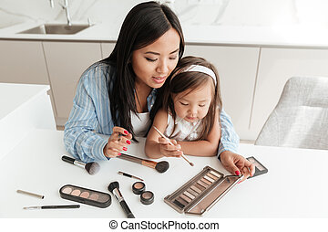 Smiling pretty asian woman doing make up while sitting with...