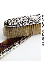 Silver brush and comb on the white background