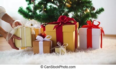 hands putting gift boxes under christmas tree - holidays,...