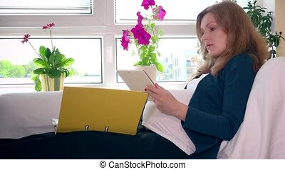 Expectant mother with tablet computer and binder working sitting on bed at home